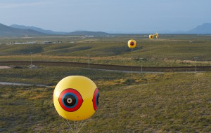 Installation detail, seen from Mexico, showing one of the balloons that comprise the Repellent Fence / Valla Repelente in relationship to the US border fence.  In this image the US Border Fence reflects the sunlight at dusk. Photo by Michael Lundgren. Courtesy of Postcommodity.