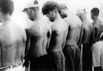 """Santiago Sierra, """"Line of 250cm Tattooed on Six Paid People,"""" 1999. Black and white photograph."""