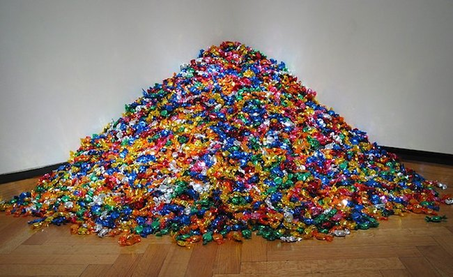 "Félix González-Torres (American, 1957–1996). ""Untitled"" (Portrait of Ross in L.A.), 1991. Candies individually wrapped in multicolored cellophane, endless supply. Overall dimensions vary with installation, ideal weight: 175 lb. The Art Institute of Chicago; promised gift of Donna and Howard Stone. Courtesy of Andrea Rosen Gallery, New York © The Félix González-Torres Foundation"